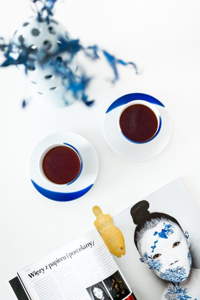 Dwa kubki herbaty na biało-niebieskich podstawkach stojące na drewnianym stole