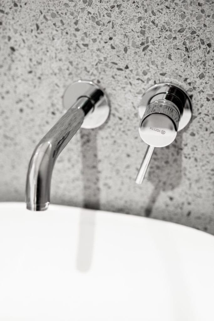 Srebrna armatura w biało-szarej łazience