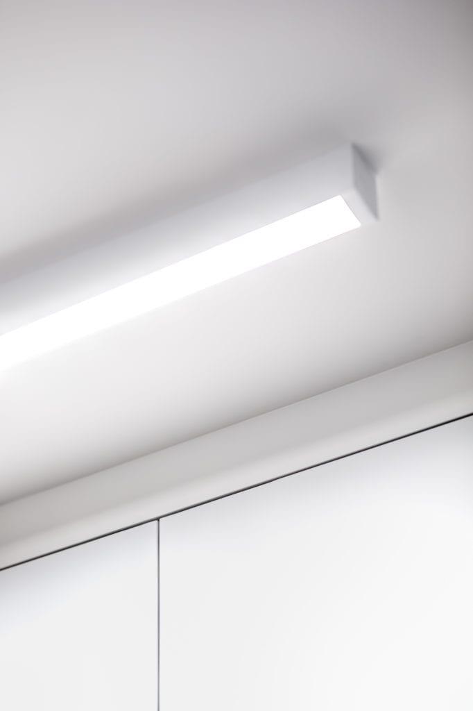 Lampa na suficie w jasnym mieszkaniu projektu Besign Studio