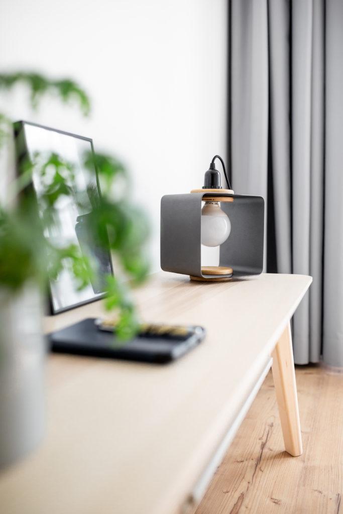 Piękna lampa stojąca na drewnianym stoliku w jasnym mieszkaniu
