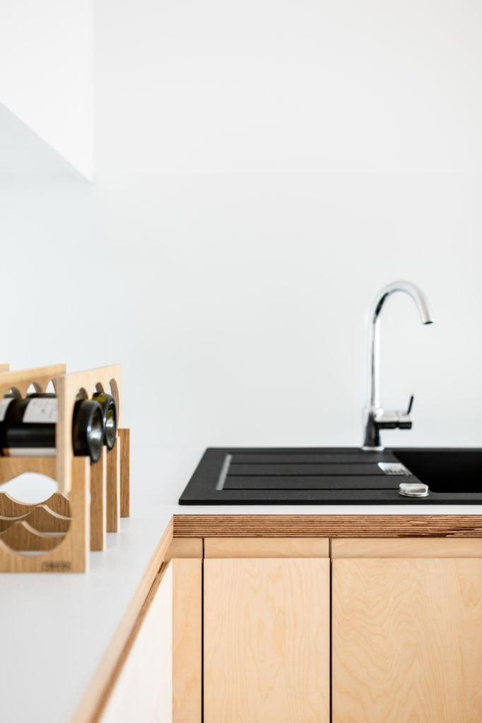 Jasna kuchnia, białe ściany, czarny zlew i drewniane dodatki