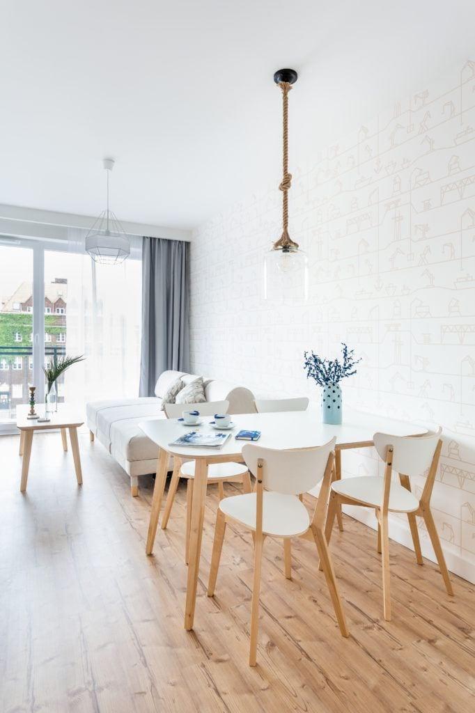 Salon, biały stół, białe krzesła, lampa ze szklanym kloszem wisząca na marynarskim sznurze
