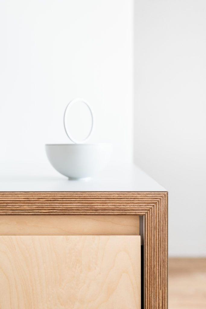Biała miska stojąca na drewnianym blacie w jasnym mieszkaniu