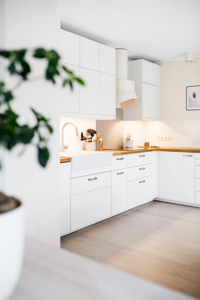 Biała kuchnia z brązowym blatem w mieszkaniu na poddaszu