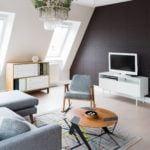 Jasne mieszkanie na poddaszu z brązową ścianą w pokoju dziennym projektu Besign Studio