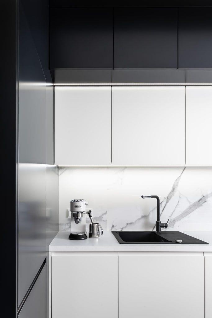 Mała kuchnia z białymi frontami projektu Besign Studio