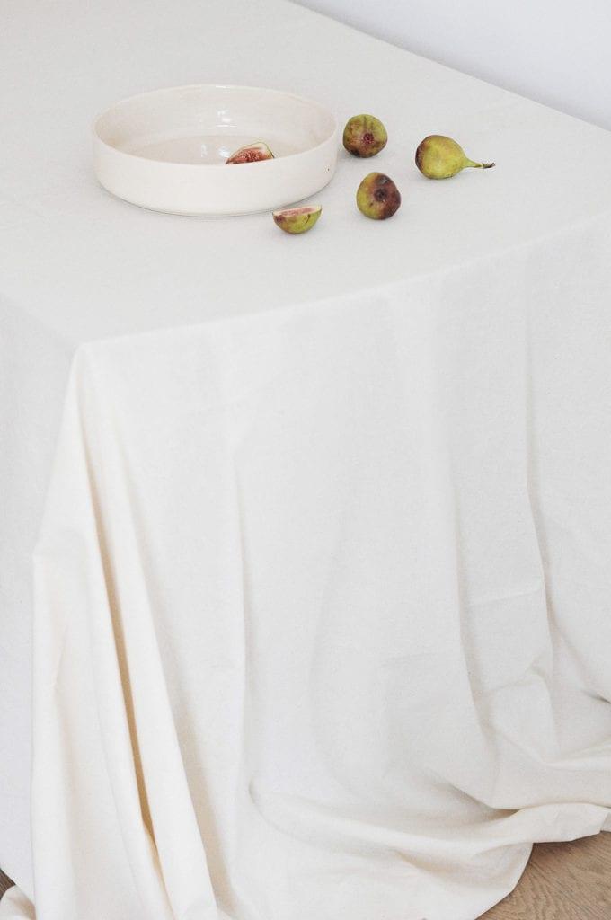 Ceramiczny talerz leżący na stole z białym obrusem