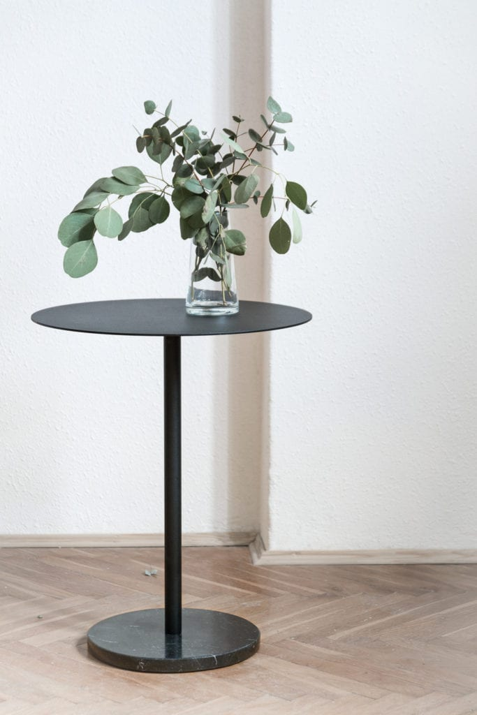 Czarny stolik pomocniczy stojący w mieszkaniu w kamienicy