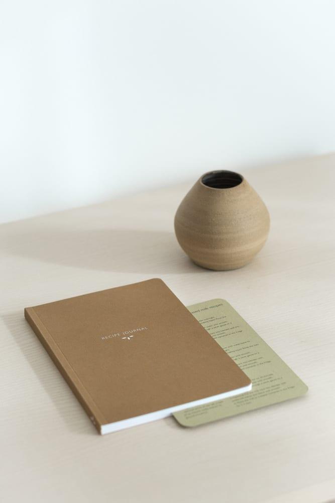 Notatnik z brązową okładką leżący na stole