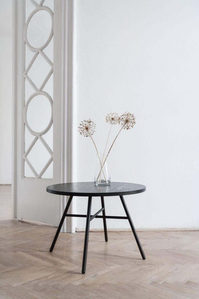 Czarny stolik od Mleko Living stojący w pokoju w kamienicy