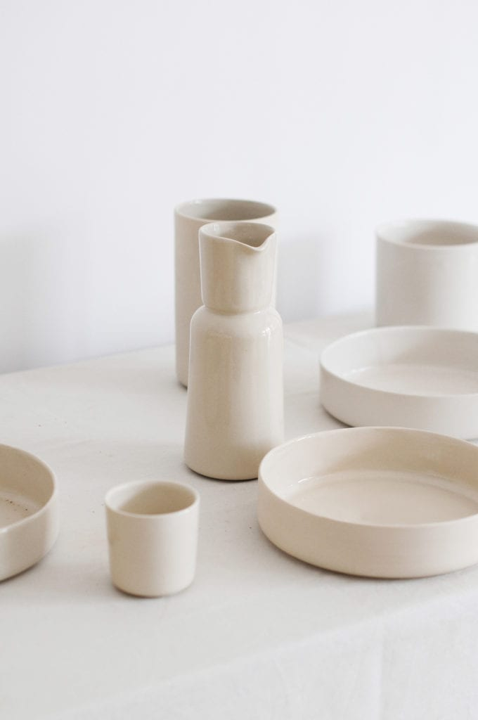 Komplet jasnej ceramicznej zastawy stojący na stole pokrytym białym obrusem