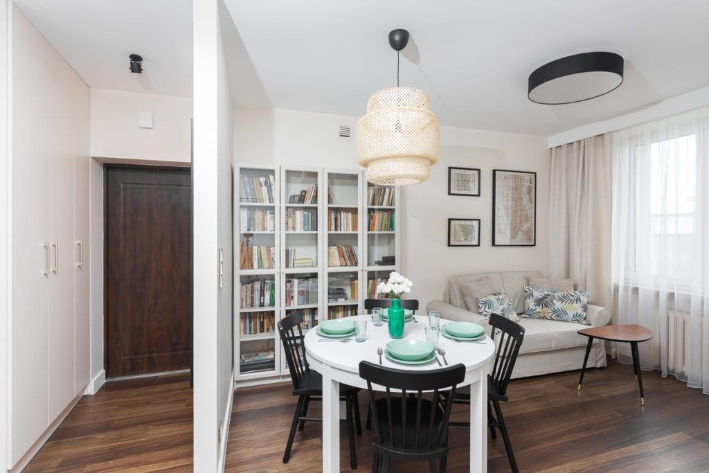 Pokój dzienny z białym stołem, czarnymi krzesłami i dużym regałem z książkami w mieszkaniu w Kielcach