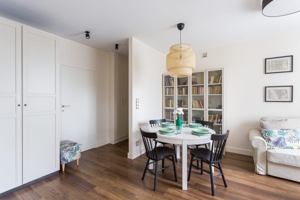 Pokój dzienny z białym stołem, czarnymi krzesłami i dużym regałem z książkami w mieszkaniu zaprojektowanym przez Clou Design