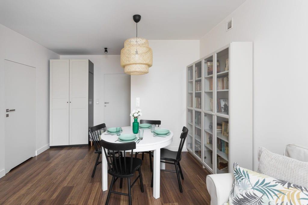 Pokój dzienny z białym stołem, czarnymi krzesłami i dużym regałem z książkami w mieszkaniu dla pary