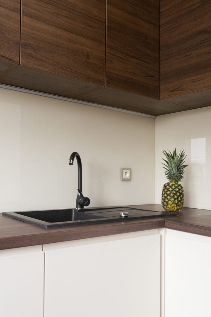 Czarny zlew w kuchni w mieszkaniu zaprojektowanym przez Clou Design