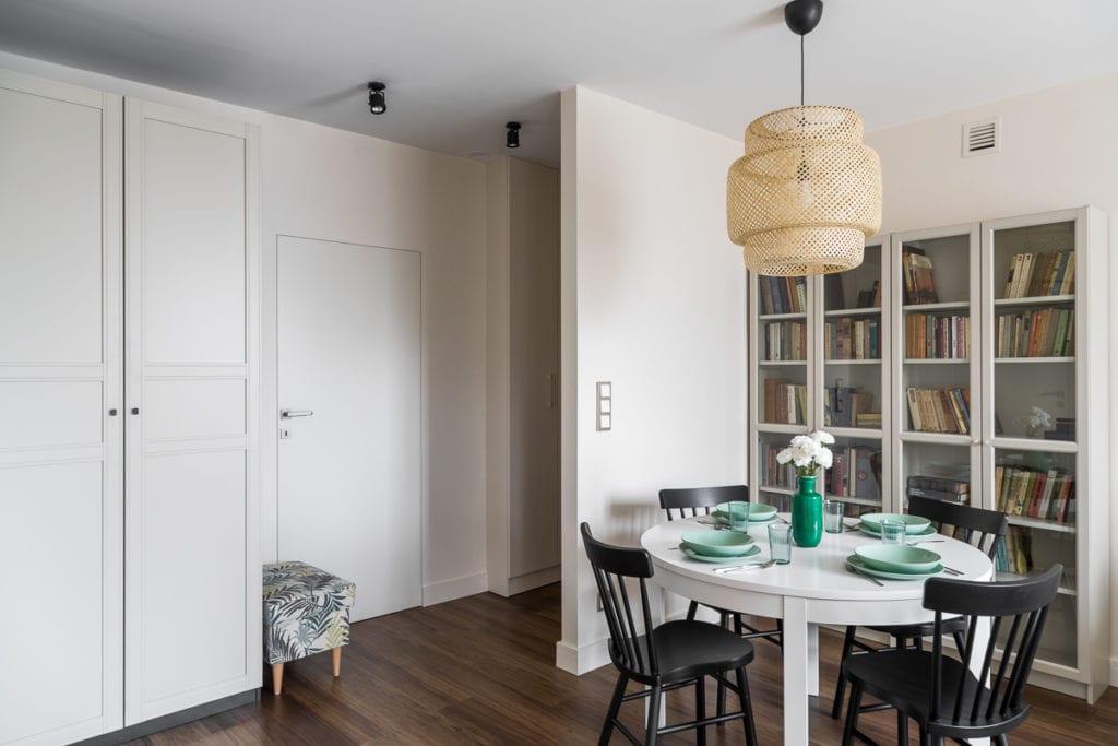 Pokój dzienny z białym stołem, czarnymi krzesłami i dużym regałem z książkami w małym mieszkaniu