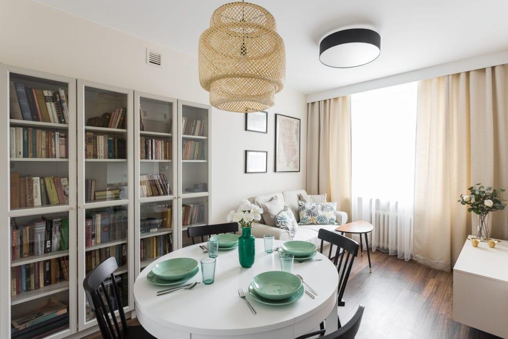 Pokój dzienny z białym stołem, czarnymi krzesłami i dużym regałem z książkami w apartamencie dla pary zaprojektowanym przez Clou Design
