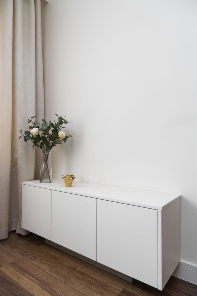 Wazon z kwiatami stojący na białej komodzie