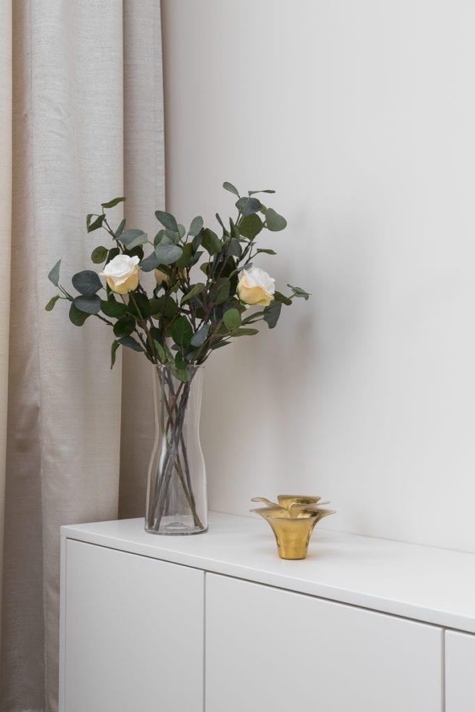Wazon z kwiatami stojący na białej komodzie w mieszkaniu zaprojektowanym przez Clou Design