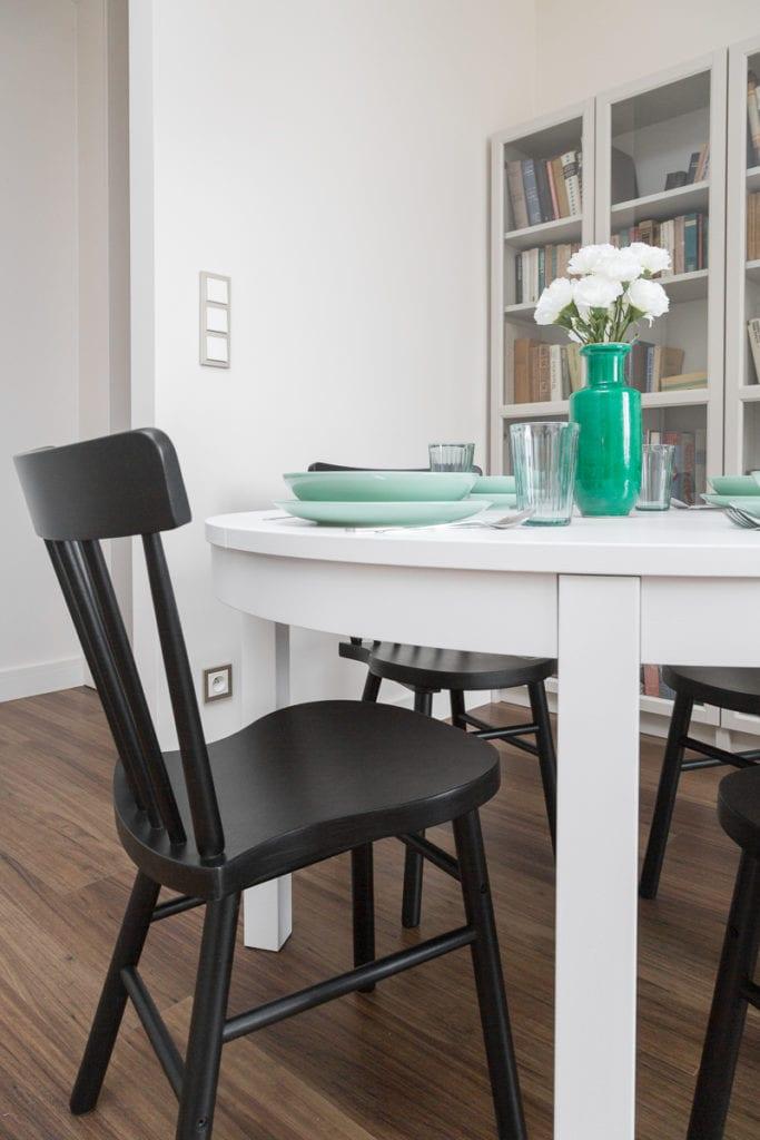 Biały stół z zieloną zastawą w mieszkaniu zaprojektowanym przez Clou Design
