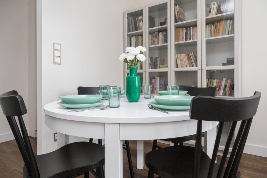Biały stół z zieloną zastawą w mieszkaniu w kamienicy