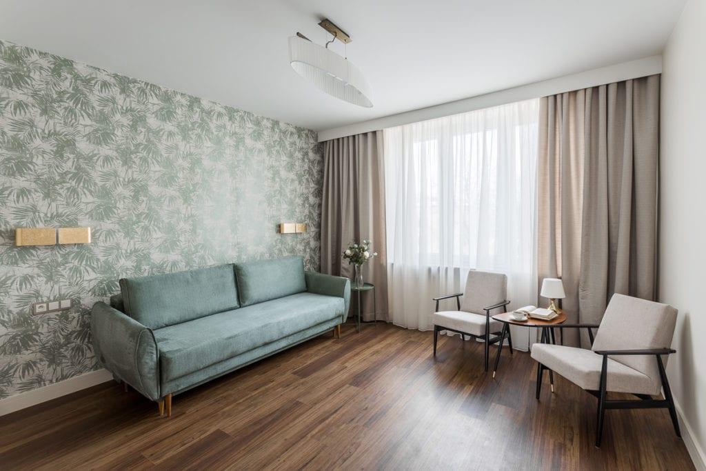 Zielona sofa i zielona tapeta w mieszkaniu zaprojektowanym przez Clou Design w Kielcach