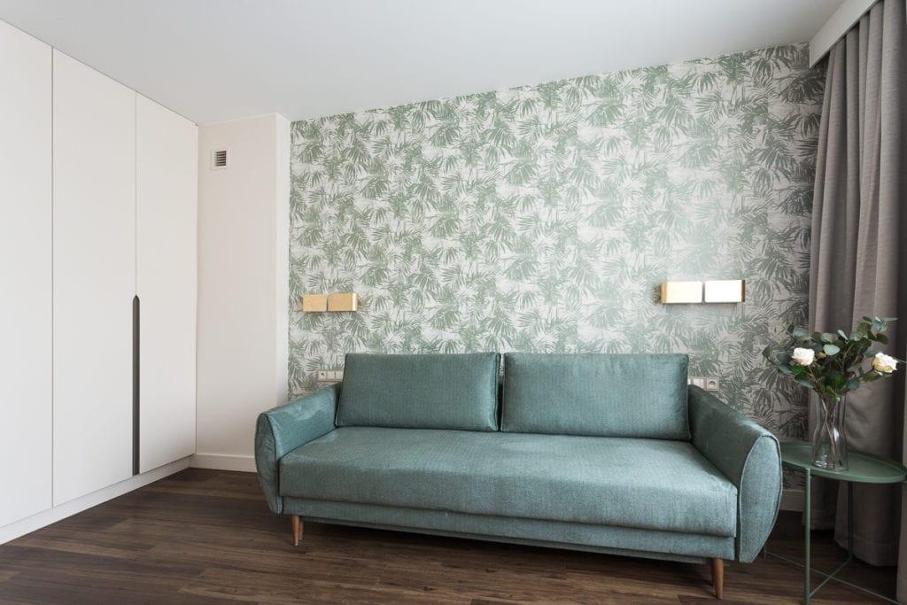 Zielona sofa i zielona tapeta w apartamencie w Kielcach