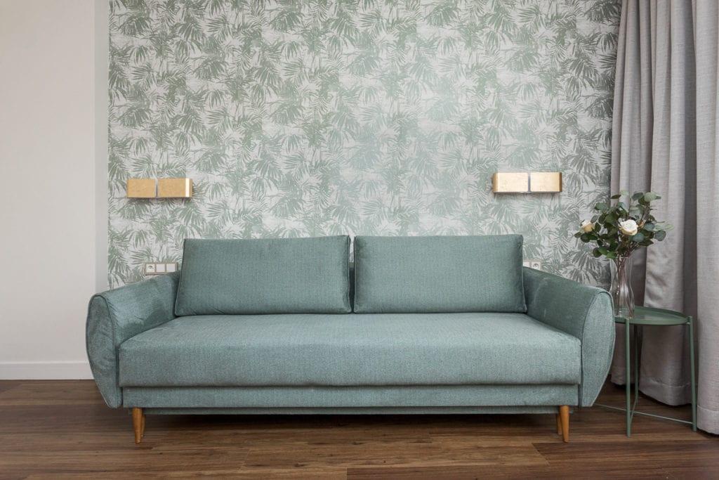 Zielona sofa i zielona tapeta w mieszkaniu zaprojektowanym przez Clou Design