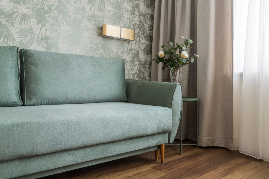 Zielona sofa i zielona tapeta w mieszkaniu dla pary
