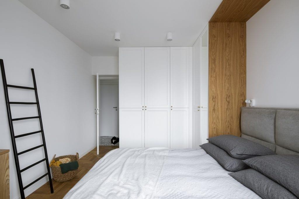 Przytulna sypialnia z dużym łóżkiem i wielką białą szafą