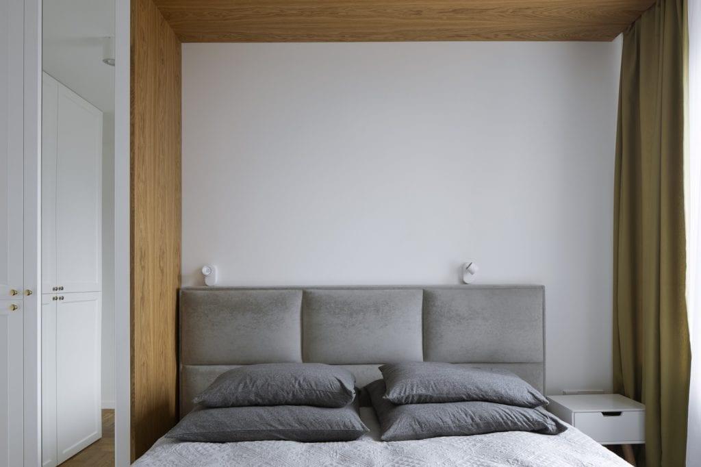 Duże łóżko w sypialni z szarym zagłówkiem
