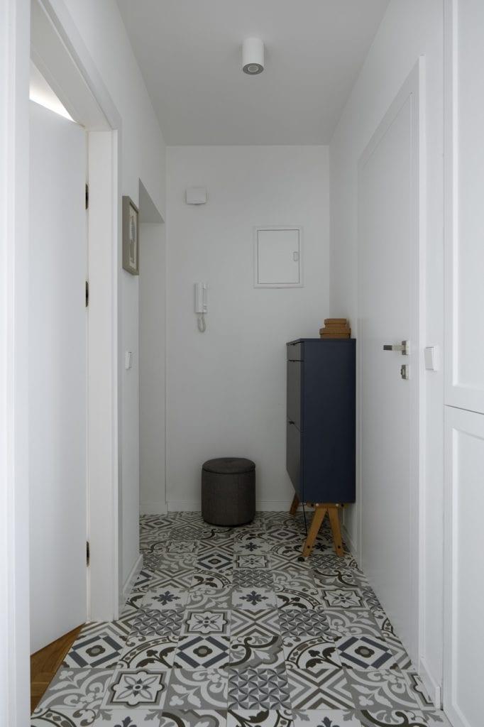Biały przedpokój z płytkami i niebieską szafką projektu MADAMA