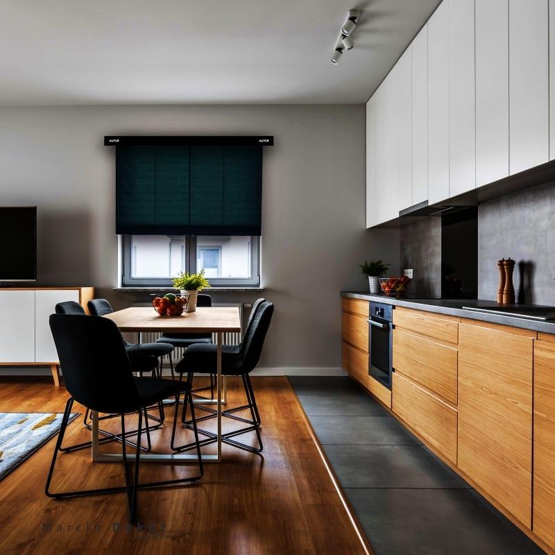 Jadalnia połączona z kuchnią i ciemne rolety w oknach