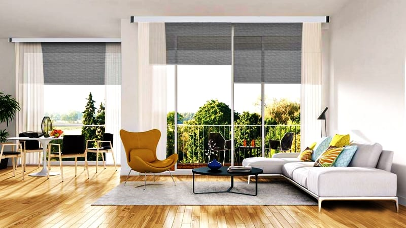 Aranżacja dekoracji okiennych w salonie z ogromnymi oknami i szarymi roletami