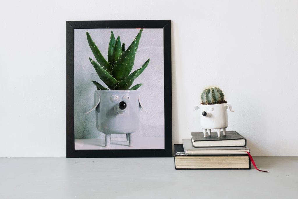 Biała doniczka w kształcie psa z rośliną