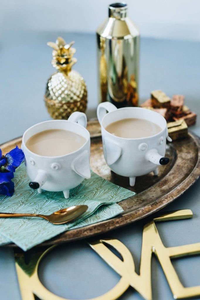 Dwa białe kubki z ceramiki w kształcie psów wypełnione kakao