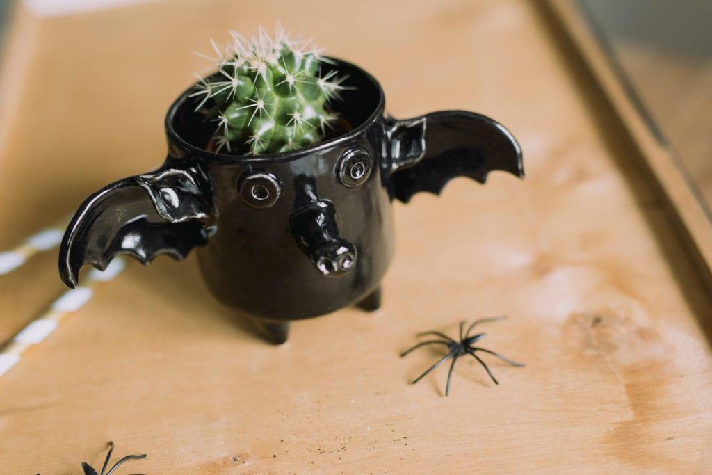 Czarny kubek z ceramiki w kształcie nietoperza stojący na stole