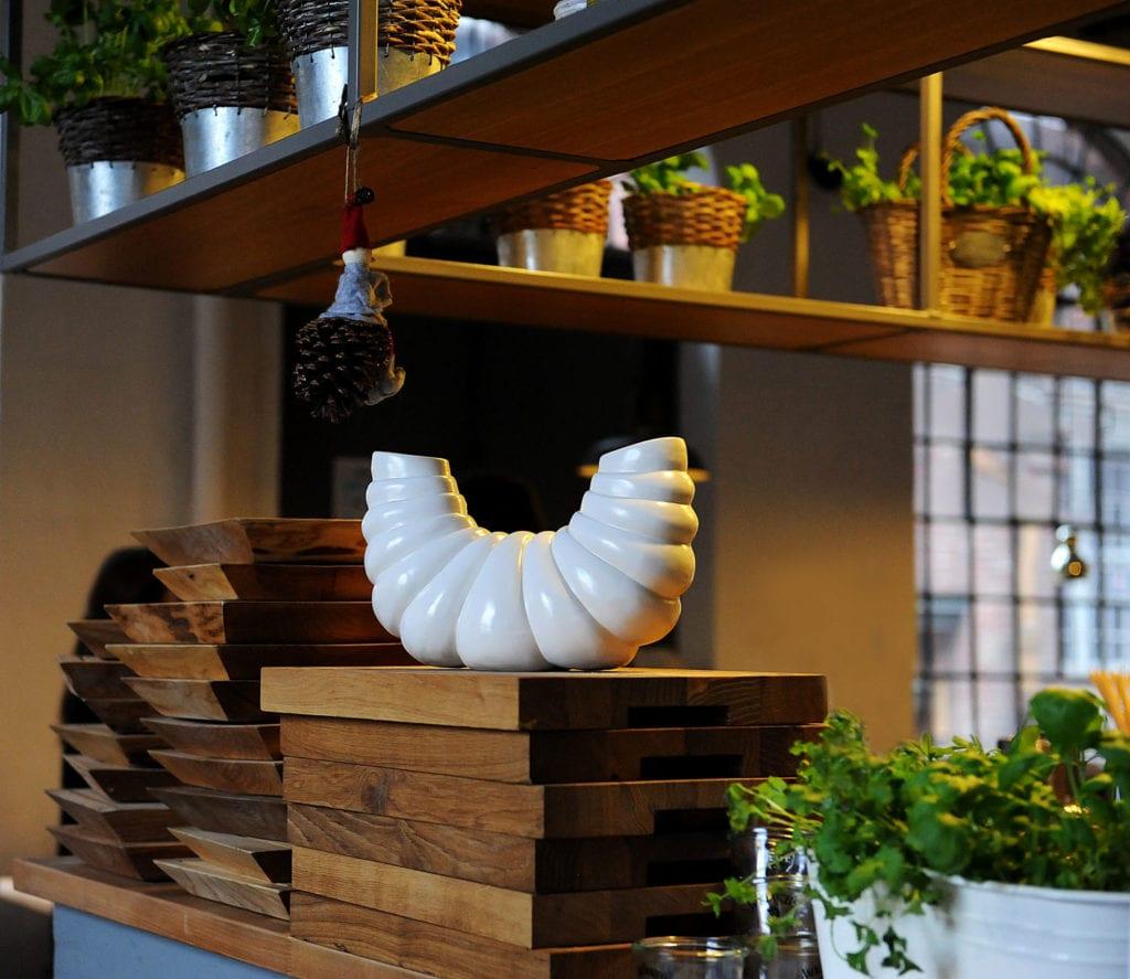 Biały wazon z ceramiki w kształcie skorupiaka stojący w kuchni od Lamabo