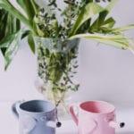 Różowy i niebieski kubek z ceramiki w kształcie psa stojące na stole