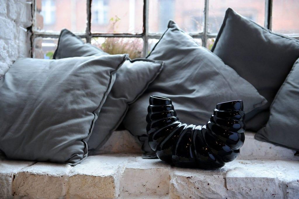 Czarny ceramiczny wazon w kształcie skorupiaka stojący na parapiecie