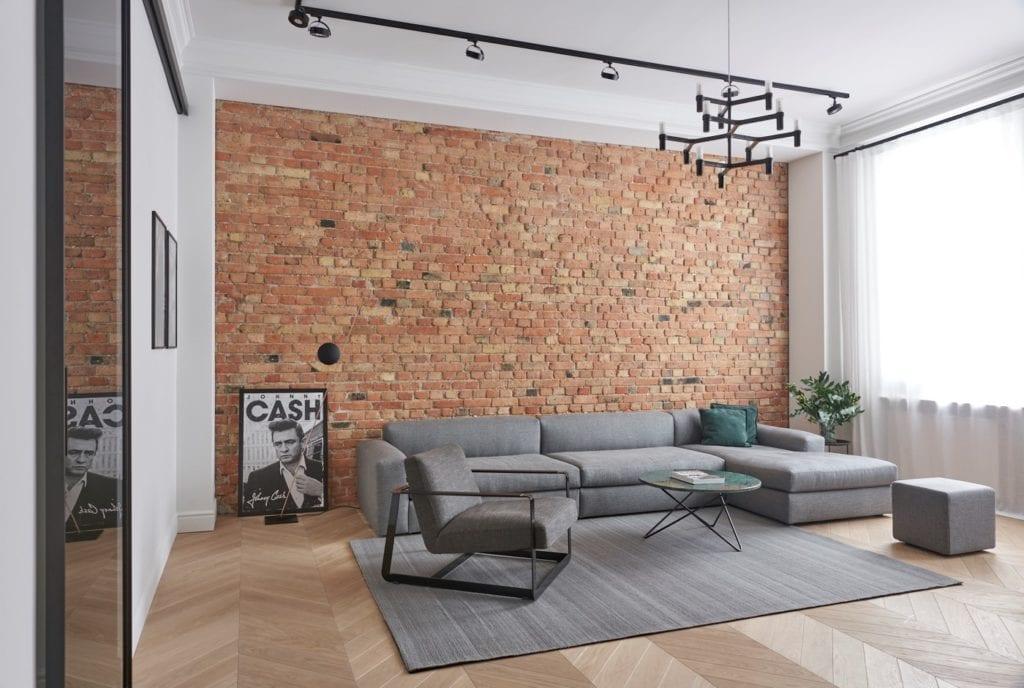 Salon z dużą, szarą sofą w apartamencie w Poznaniu projektu Studio Forma 96