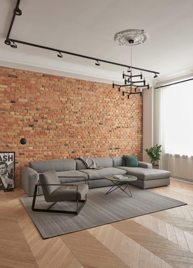 Salon ze ścianą z cegły w apartamencie w Poznaniu projektu Studio Forma 96
