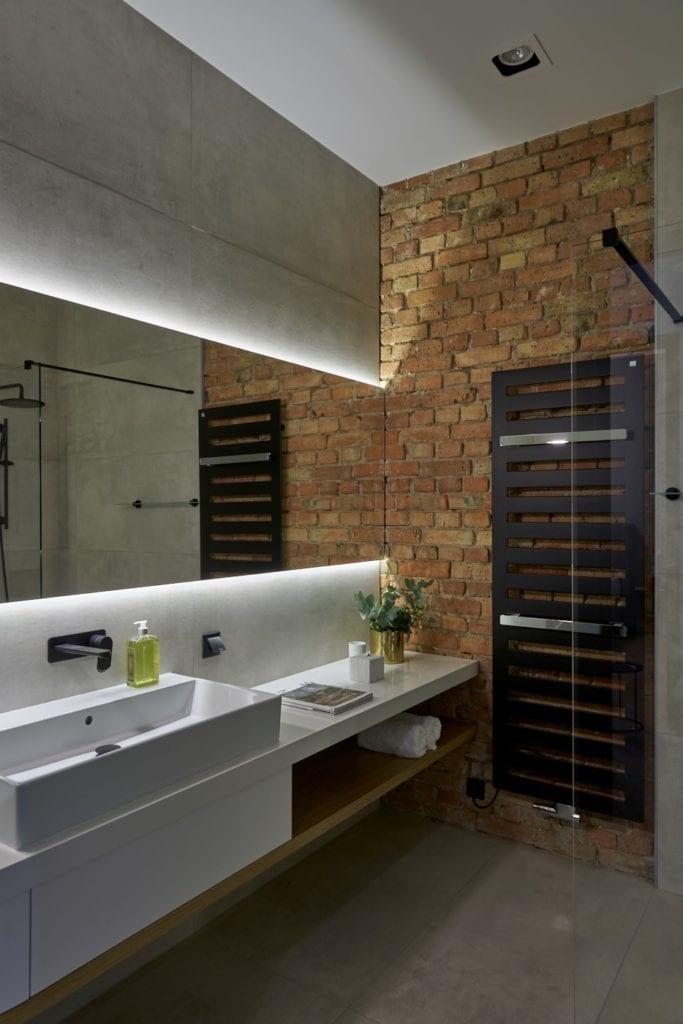 Łazienka ze ścianą z cegływ apartamencie w Poznaniu projektu Studio Forma 96