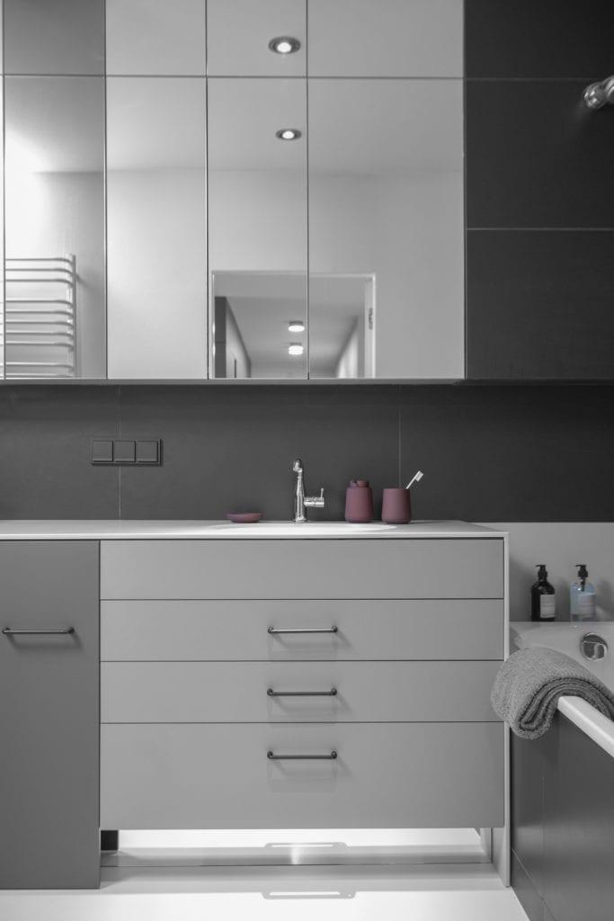 Szare i białe szafki w łazience w mieszkaniu