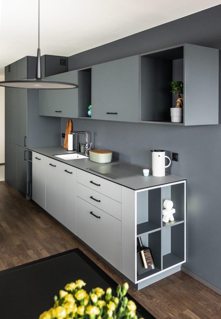 Biała zabudowa kuchni z szarym blatem w mieszkaniu zaprojektowanym przez Kasia Orwat Design