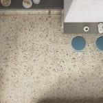 Beżowe lastrico z brązowymi kropkami na podłodze w kuchni