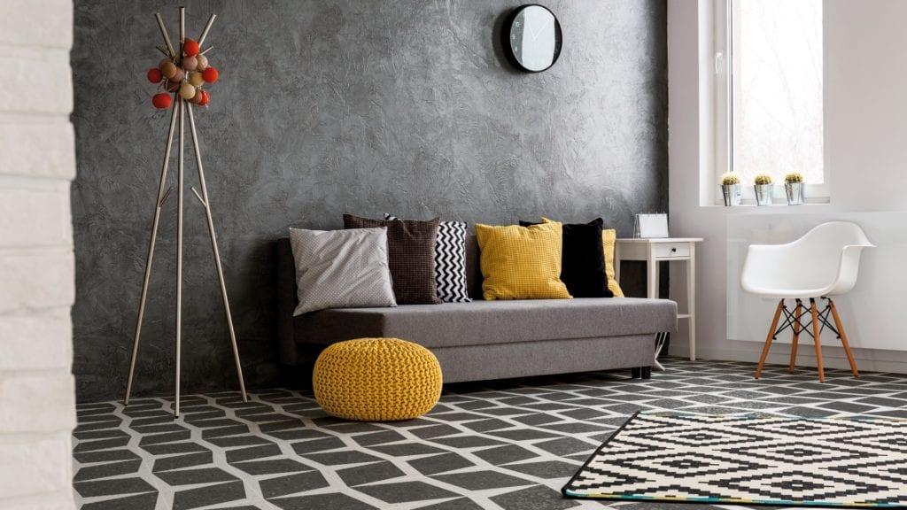 Szara ściana w pokoju, szara sofa i podłoga z lastryko