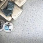 Jasna sofa stojąca na podłodze z lastryko