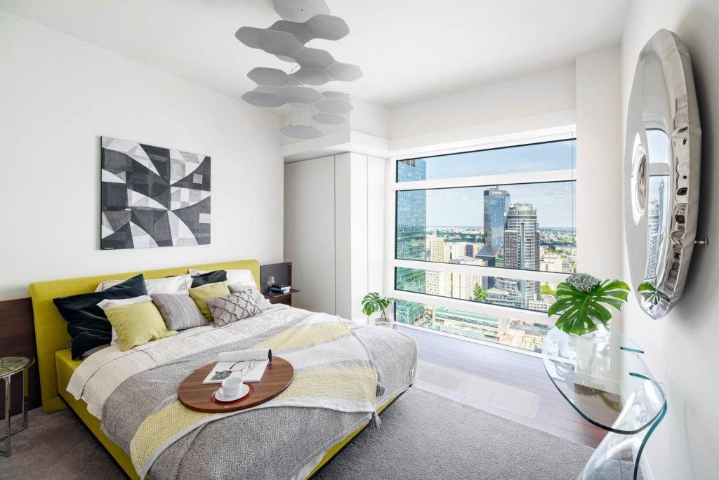 Sypialnia z pięknym widokiem na Warszawę w apartamencie GLACE projektu pracowni AKSONOMETRIA