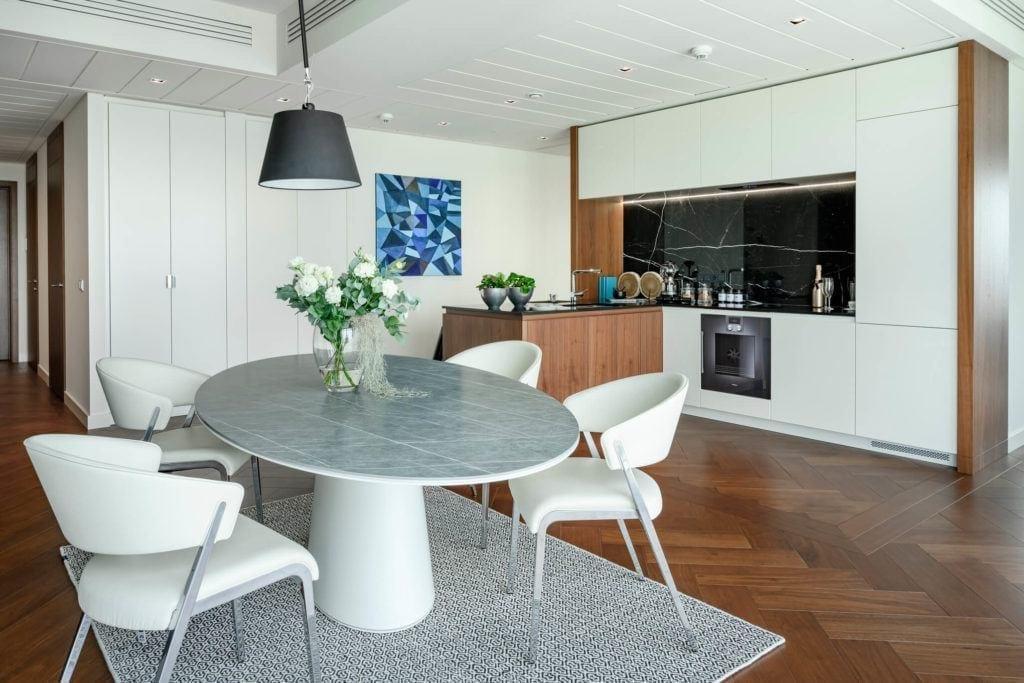 Jadalnia z dużym stołem w apartamencie GLACE projektu pracowni AKSONOMETRIA
